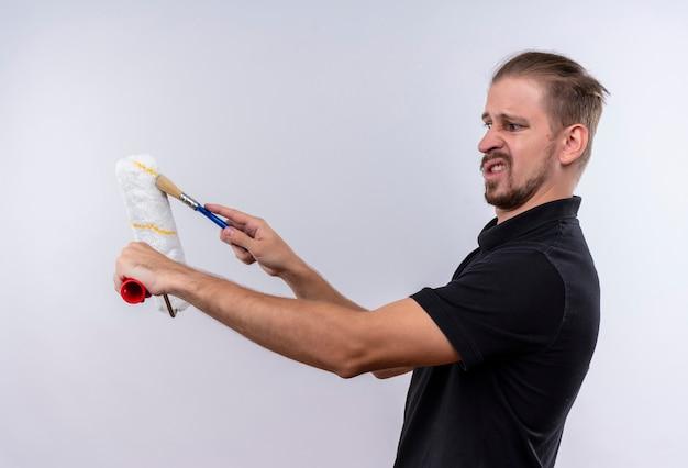 Jovem bonito em uma camisa pólo preta segurando um rolo de pintura e um pincel olhando para eles com expressão de nojo em pé sobre um fundo branco