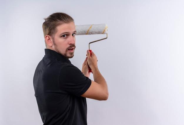 Jovem bonito em uma camisa pólo preta segurando um rolo de pintura vai pintar uma parede de pé sobre um fundo branco