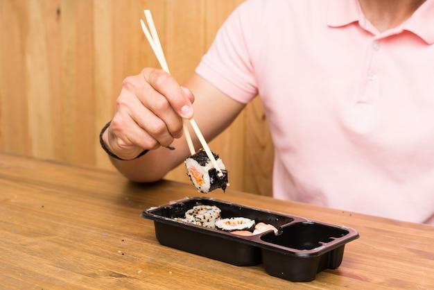 Jovem bonito em uma cozinha com sushi