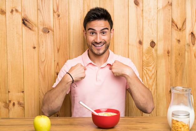 Jovem bonito em uma cozinha tomando café da manhã com expressão facial de surpresa