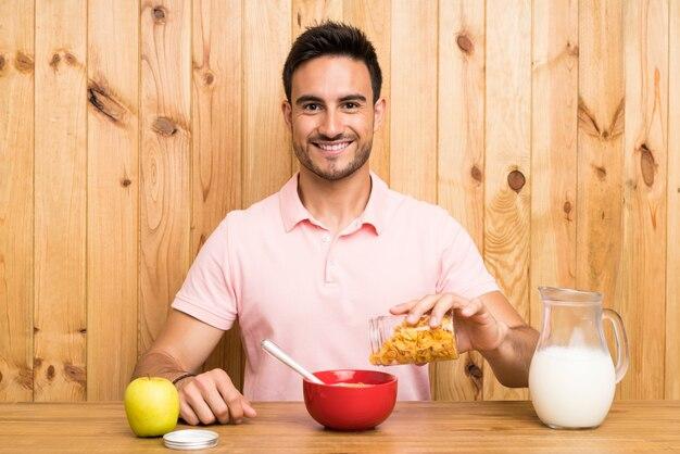 Jovem bonito em uma cozinha tomando café da manhã