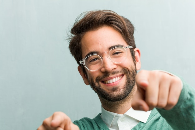Jovem bonito empreendedor homem cara closeup alegre e sorridente apontando para a frente