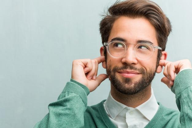 Jovem, bonito, empreendedor, homem, rosto, closeup, cobertura, orelhas, com, mãos