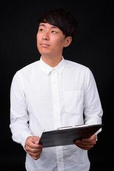 Jovem bonito empresário asiático no preto