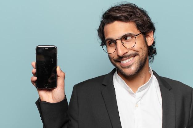 Jovem bonito empresário indiano mostrando a tela vazia do telefone