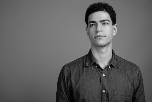 Jovem bonito empresário persa contra uma parede cinza em preto e branco
