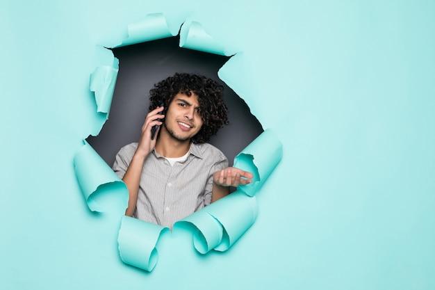 Jovem bonito encaracolado falar ao telefone do buraco no papel verde