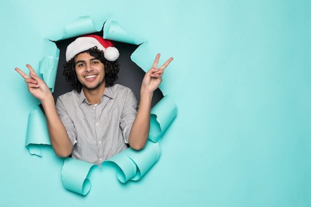 Jovem bonito encaracolado usar chapéu de papai noel com gesto de paz de buraco no papel verde