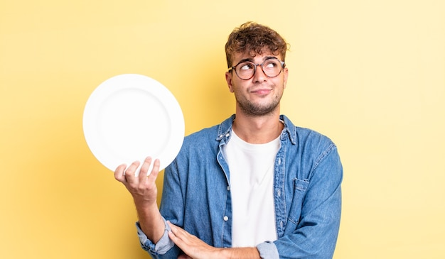 Jovem bonito encolhendo os ombros, sentindo-se confuso e incerto. conceito de prato vazio