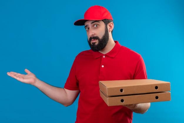 Jovem, bonito, entregador, caucasiano, impressionado, vestindo um uniforme vermelho e boné, segurando caixas de pizza e mostrando a mão vazia isolada no azul