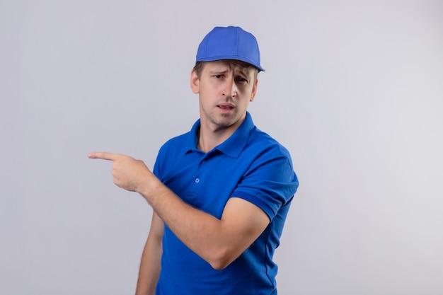 Jovem bonito entregador de uniforme azul e boné apontando com o dedo indicador para o lado, parecendo confuso em pé sobre uma parede branca