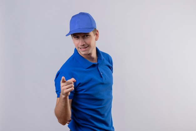 Jovem bonito entregador de uniforme azul e boné apontando para a câmera com o dedo indicador parecendo confiante em pé sobre uma parede branca