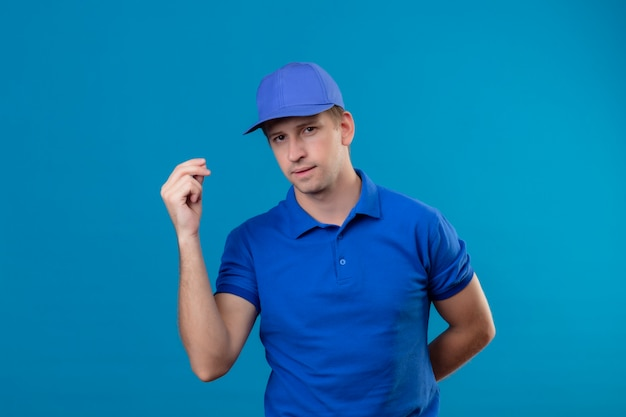 Jovem bonito entregador de uniforme azul e boné com cara séria fazendo gesto de dinheiro com a mão em pé sobre a parede azul