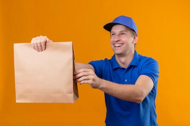 Jovem bonito entregador de uniforme azul e boné dando um pacote de papel para um cliente