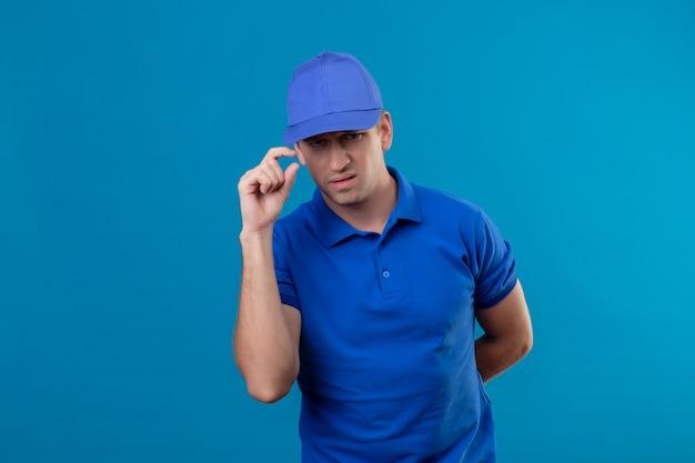 Jovem bonito entregador de uniforme azul e boné descontente em tocar em seu boné com o rosto carrancudo de pé sobre a parede azul