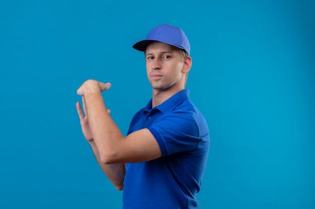 Jovem bonito entregador de uniforme azul e boné fazendo gesto de pausa com as mãos com cara séria em pé sobre a parede azul