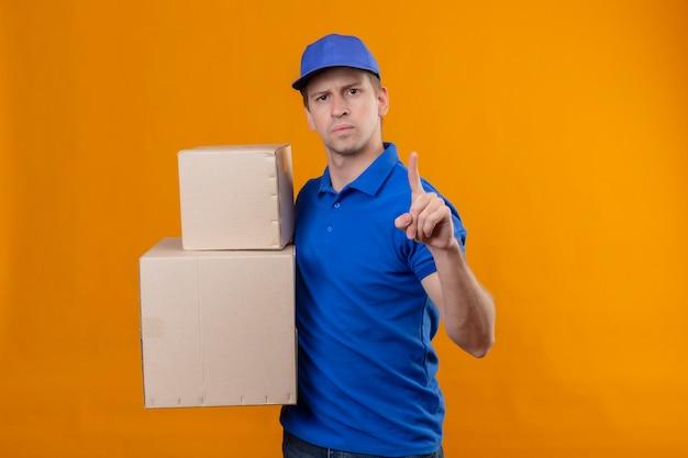 Jovem bonito entregador de uniforme azul e boné segurando caixas de papelão apontando o dedo para cima, aviso com expressão séria no rosto em pé sobre a parede laranja