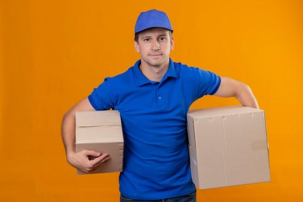 Jovem bonito entregador de uniforme azul e boné segurando caixas de papelão com um sorriso confiante no rosto em pé sobre a parede laranja