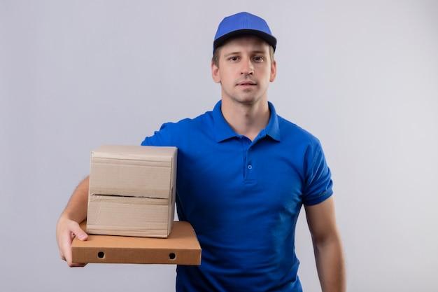 Jovem bonito entregador de uniforme azul e boné segurando caixas de pizza com expressão confiante no rosto em pé sobre uma parede branca