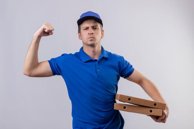 Jovem bonito entregador de uniforme azul e boné segurando caixas de pizza levantando o punho e mostrando o bíceps