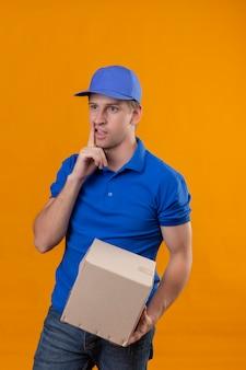 Jovem bonito entregador de uniforme azul e boné segurando o pacote da caixa olhando para o lado com uma expressão pensativa no rosto pensando tendo dúvidas em pé sobre a parede laranja