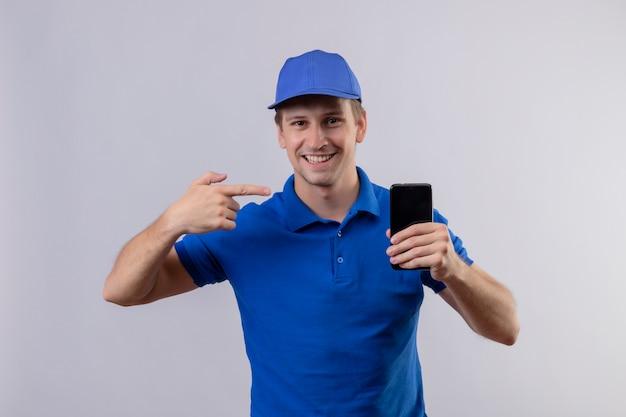 Jovem bonito entregador de uniforme azul e boné segurando um celular apontando com o dedo para ele e sorrindo amigável em pé sobre uma parede branca
