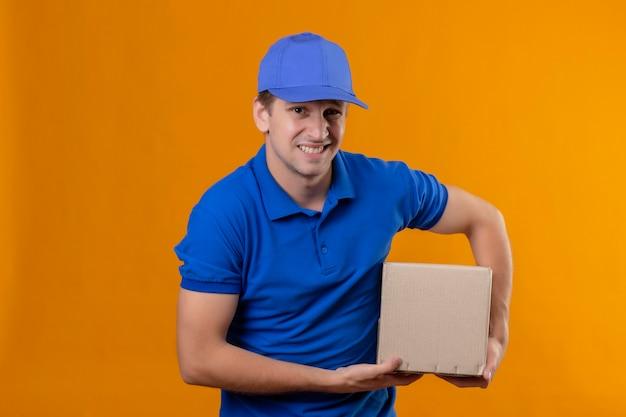 Jovem bonito entregador de uniforme azul e boné segurando um pacote de caixa descontente com uma expressão de nojo