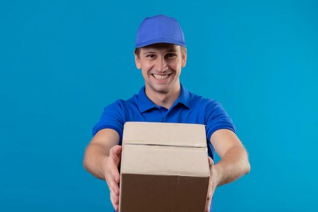 Jovem bonito entregador de uniforme azul e boné segurando um pacote de caixa, sorrindo alegremente