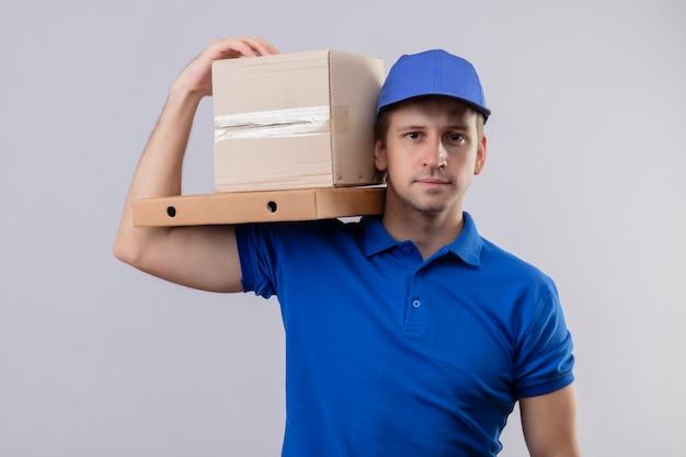 Jovem bonito entregador de uniforme azul e boné segurando uma caixa no ombro com uma expressão confiante no rosto em pé sobre uma parede branca