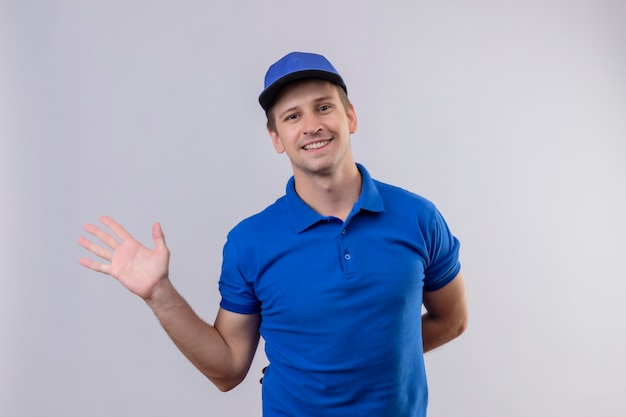 Jovem bonito entregador de uniforme azul e boné sorrindo amigável fazendo gesto de saudação acenando com a mão em pé sobre a parede branca