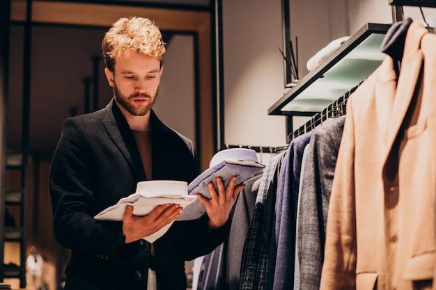 Jovem bonito, escolhendo a camisa em uma loja