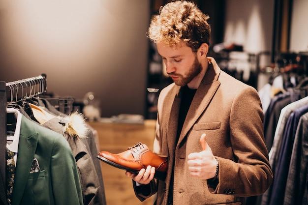 Jovem bonito, escolhendo sapatos em uma loja
