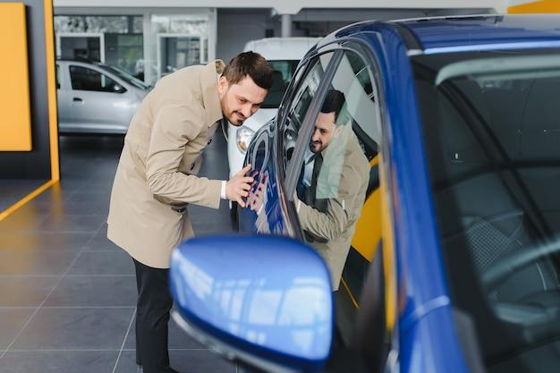 Jovem bonito escolhendo um carro em um showroom de carros