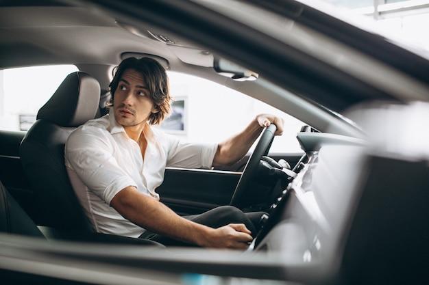 Jovem bonito, escolhendo um carro em uma sala de exposições