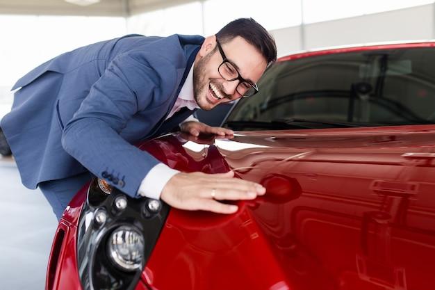 Jovem bonito escolhendo um carro novo no showroom de carros.