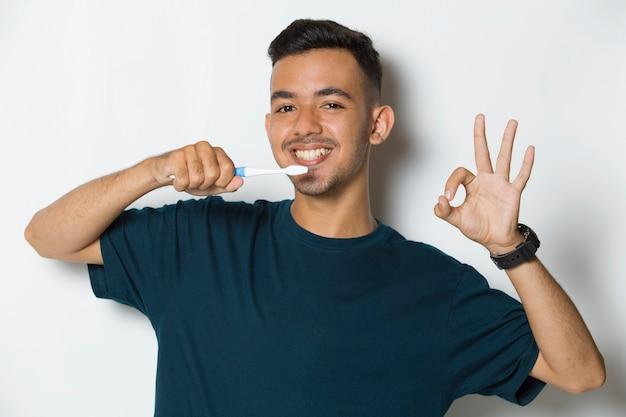 Jovem bonito escovando os dentes isolados no fundo branco