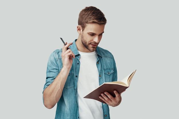 Jovem bonito escrevendo algo em pé contra um fundo cinza