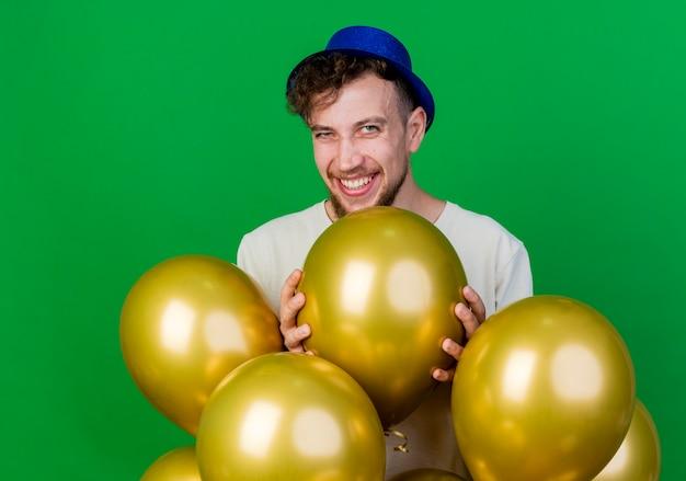 Jovem bonito eslavo festeiro alegre com chapéu de festa em pé atrás de balões, olhando para a câmera, segurando um balão isolado sobre fundo verde