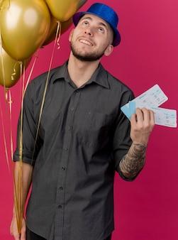Jovem bonito eslavo festeiro sorridente com chapéu de festa segurando balões e passagens de avião olhando para cima isolado no fundo carmesim