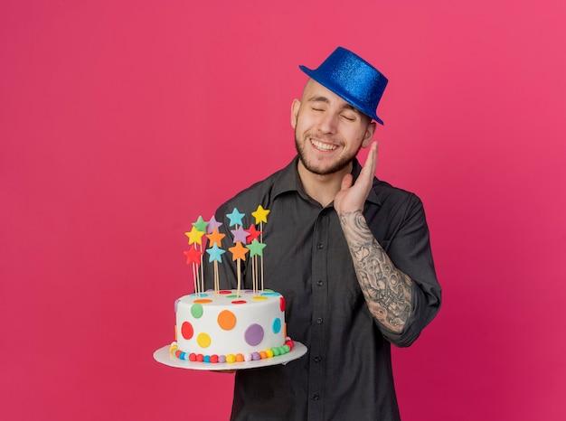 Jovem bonito eslavo festeiro sorridente com chapéu de festa segurando um bolo de aniversário com estrelas, mantendo as mãos no ar com os olhos fechados, isolado em um fundo carmesim com espaço de cópia