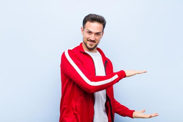 Jovem bonito esportes homem ou monitor segurando um objeto com as duas mãos no espaço lateral da cópia, mostrando, oferecendo ou anunciando um objeto contra a parede plana