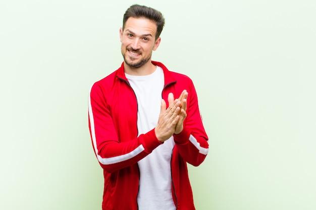 Jovem bonito esportes homem ou monitor, sentindo-se feliz e bem sucedido, sorrindo e batendo palmas de mãos, dizendo parabéns com um aplauso contra parede verde