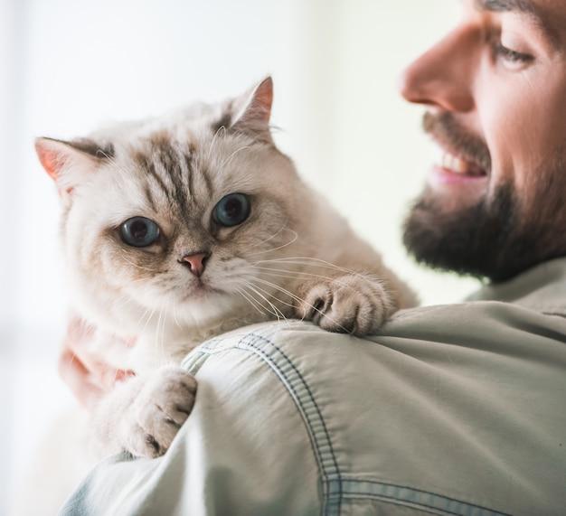 Jovem bonito está segurando um gato bonito.