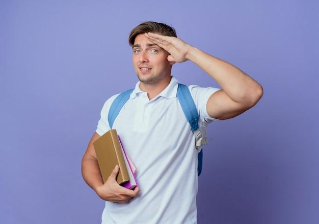 Jovem bonito estudante satisfeito usando uma bolsa de costas segurando livros e mostrando um gesto de saudação isolado no azul