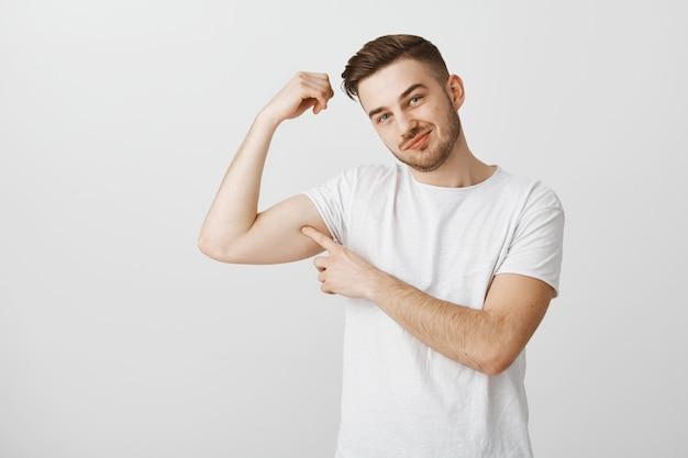 Jovem bonito exibe sua força indo à academia para se exercitar, flexionando os músculos e sorrindo com orgulho