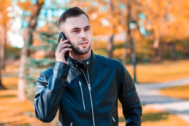 Jovem bonito falando ao telefone no belo parque de outono. rapaz jovem usando smartphone para uma chamada ao ar livre em dia de sol