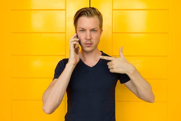 Jovem bonito falando no celular e apontando o dedo na frente da porta amarela