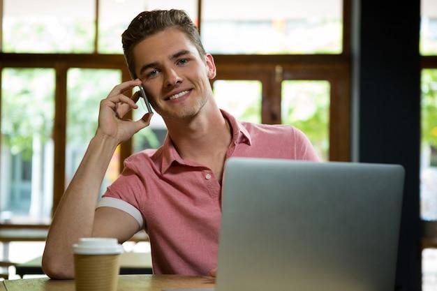 Jovem bonito falando no celular em um café
