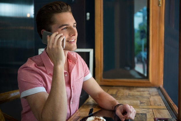 Jovem bonito falando no celular em uma cafeteria