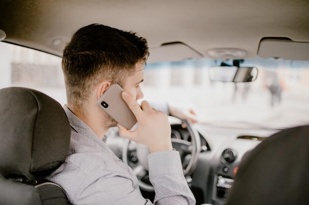 Jovem bonito falando no celular enquanto estiver dirigindo e ultrapassando, não prestando atenção à estrada e ao tráfego.